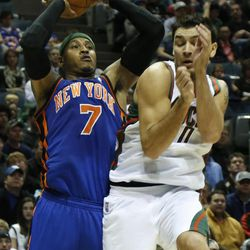 New York Knicks' Carmelo Anthony (7) puts up a shot against Milwaukee Bucks' Carlos Delfino, right, during the first half of an NBA basketball game on Wednesday, April 11, 2012, in Milwaukee.