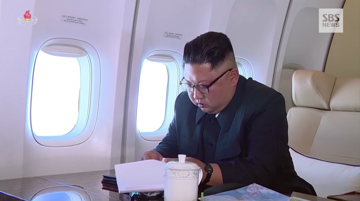 Kim Jong Un reads papers on the plane while flying to Singapore.