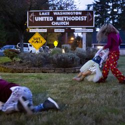 Adrianna Branstetter, 3, crawls around in the grass as sister Lucy, 6, swings around Julianna, 1, as they play outside before dunner at Lake Washington United Methodist Church in Kirkland, Wash., on Sunday, Oct. 13, 2019. The girls and their parents, Crissy Norton and Matthew Branstetter, have been using the church's Safe Parking program for the past several months.