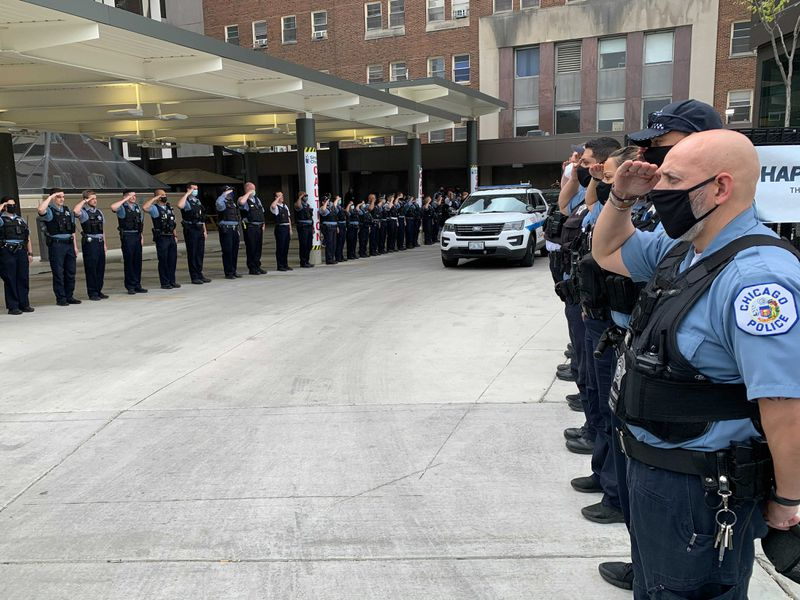 Members of the police department salute the two wounded officers after they were discharged from Mt. Sinai, May 16, 2021. Tom Schuba/Sun-Times