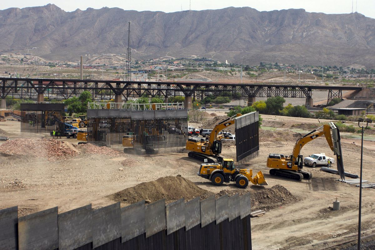 Heavy machinery moves sections of border wall into place in a sandy section of land on the US-Mexico border.