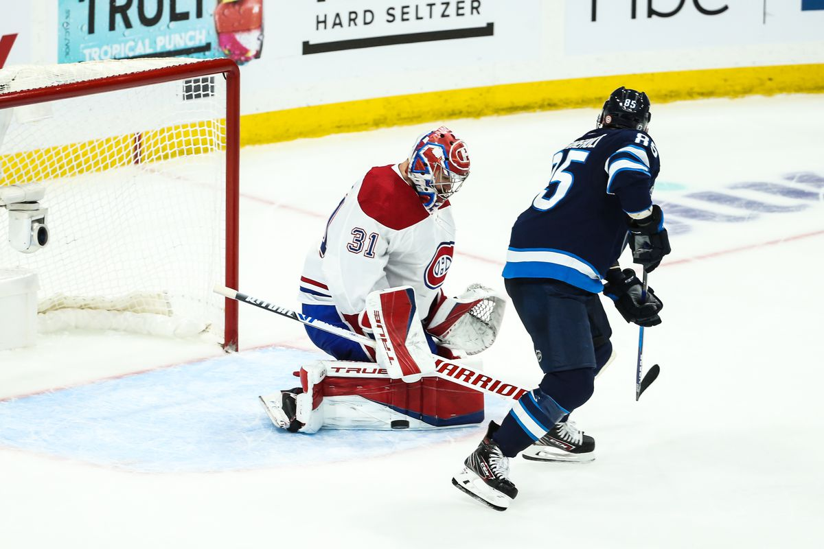 Montreal Canadiens goalie Carey Price (31) makes a save with Winnipeg Jets forward Matthieu Perreault (85) looking for a rebound during the third period in game two of the second round of the 2021 Stanley Cup Playoffs at Bell MTS Place.