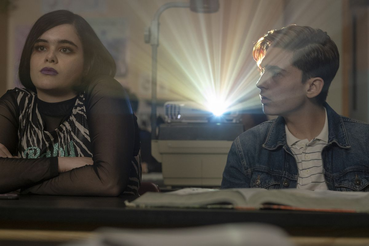 A boy in a denim jacket with light brown hair and a striped white shirt stares at the girl to his right, who looks forward blankly while wearing a mesh long-sleeve shirt and zebra print tank. They're both backlit by the light of a projector.