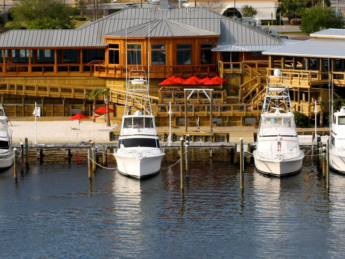 Large white cruisers line the dock at Boshamps Seafood and Oyster House in Destin, FL.