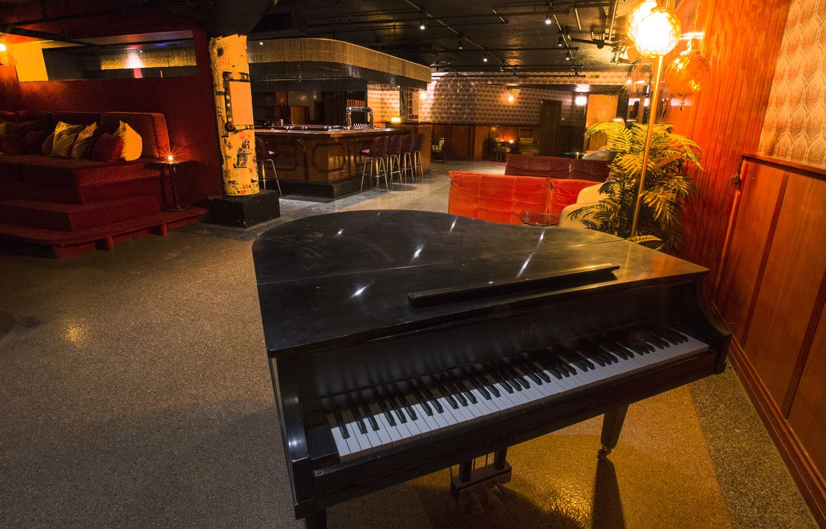 A black baby grand piano in front of a bar.