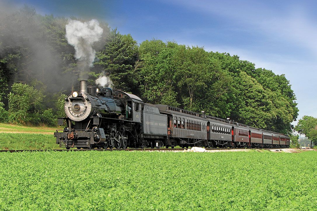 A train rides along a track. There is smoke billowing out of the first car of the train. There are trees and grass surrounding the track.