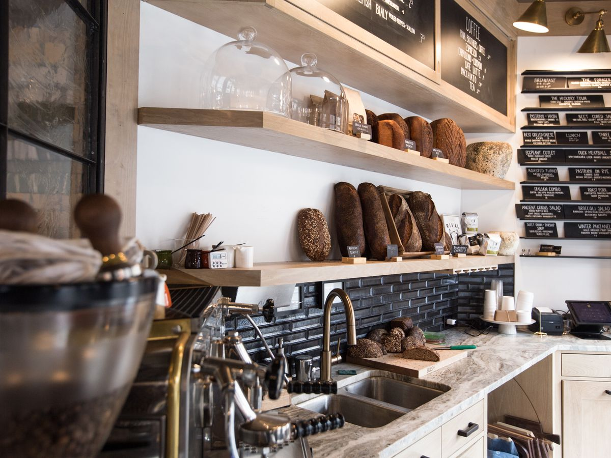 The interior of a bakery, with kitchen equipment and loaves of assorted colors and shapes of bread leaned against a far wall
