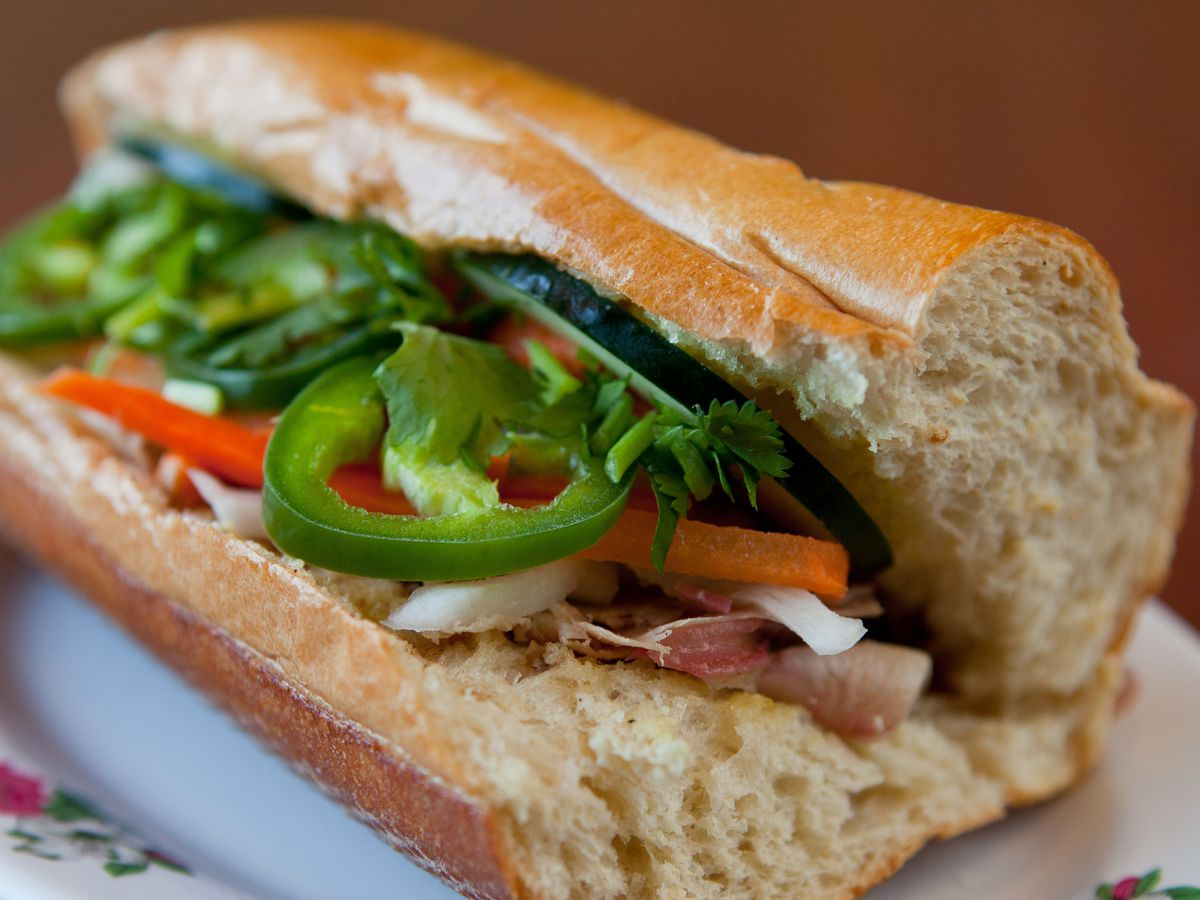 A close-up on a banh mi sandwich, stuffed with sliced green peppers, carrot, and meat