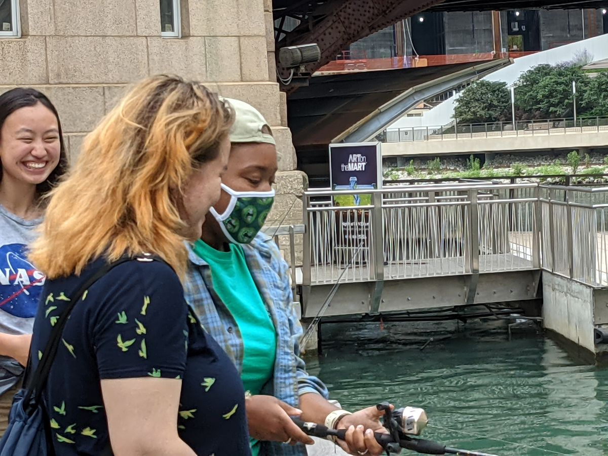 """Destiny Berry (with mask) teaches a visitor to """"Fishing at the Jetty"""" the basics of fishing from the Chicago Riverwalk. Credit: Dale Bowman"""
