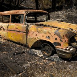 A burned out car sits on Stagecoach Canyon Road after a wildfire in Santa Margarita, Calif., Wednesday, June 28, 2017.