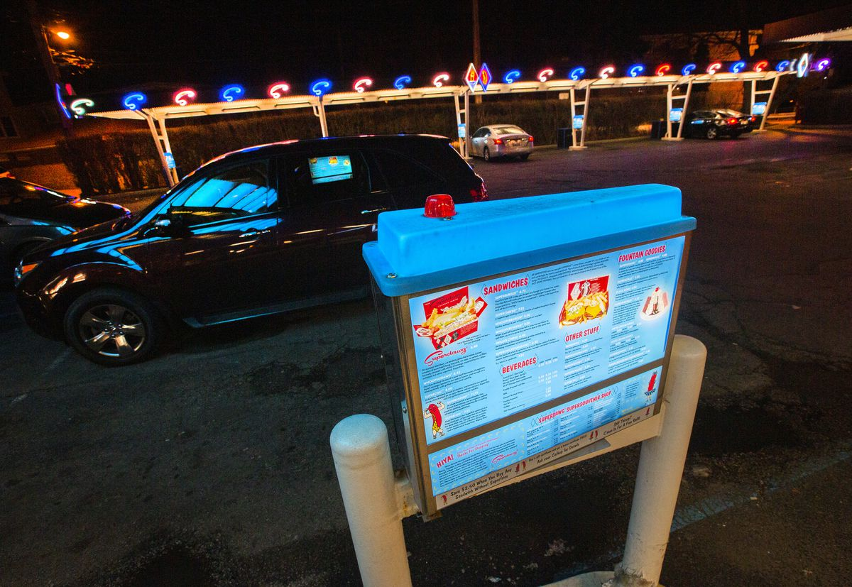 A drive-in's menu that's light up in parking lot.