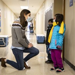 Preschool teacher Erin Berry greets two students as they walk into Dawes Elementary School at 3810 W. 81st Pl. on the Southwest Side, Monday morning, Jan. 11, 2021.
