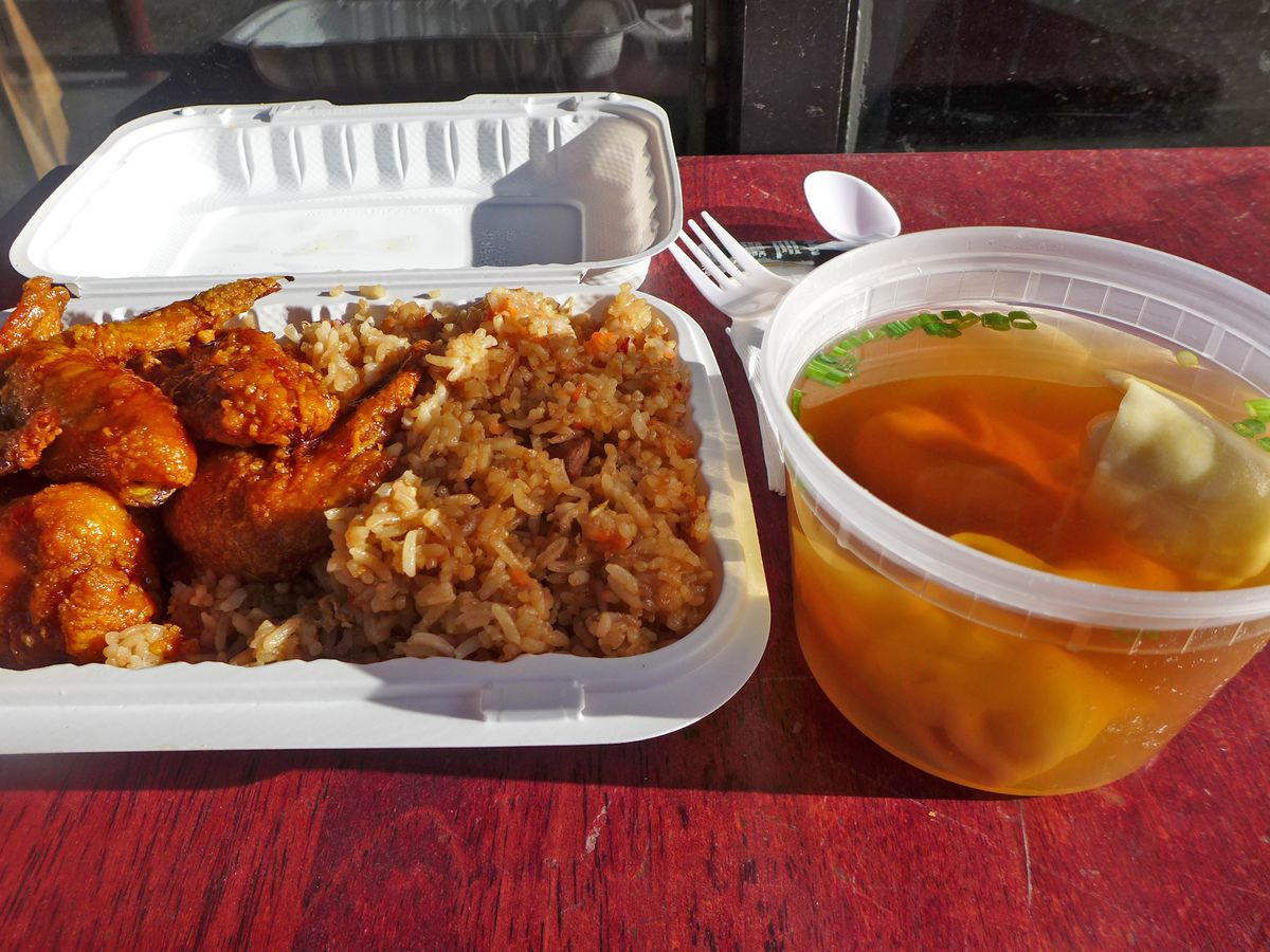 A white carryout container with chicken wings on one side and fried rice on the other with some translucent brown wonton soup on the side.