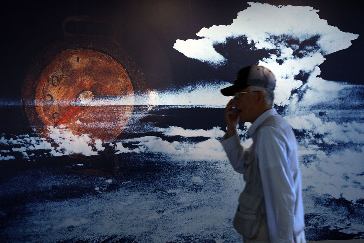 A man standing in front of wall-sized picture of an atomic mushroom cloud.