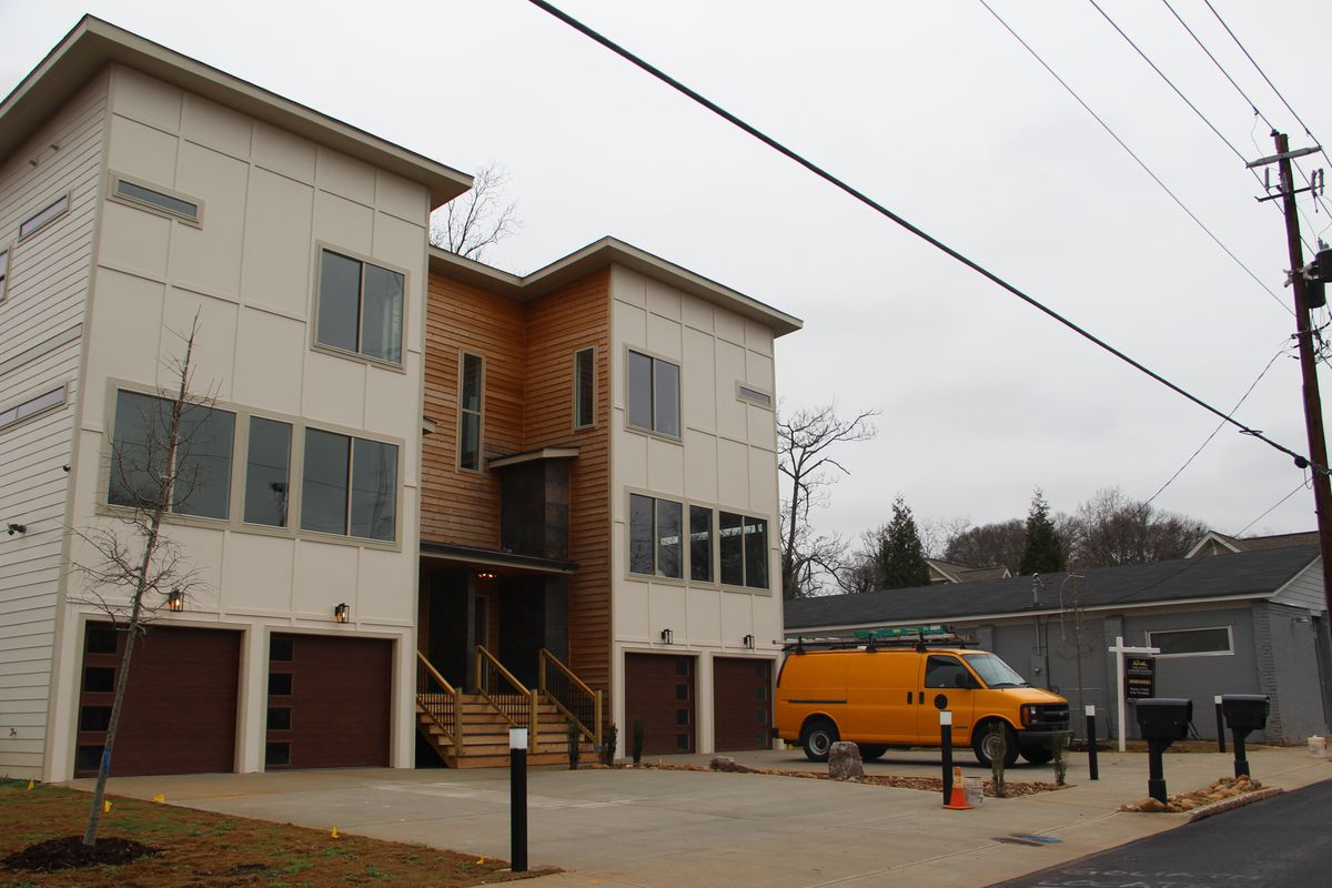 Two townhome units with an orange van parked in front.