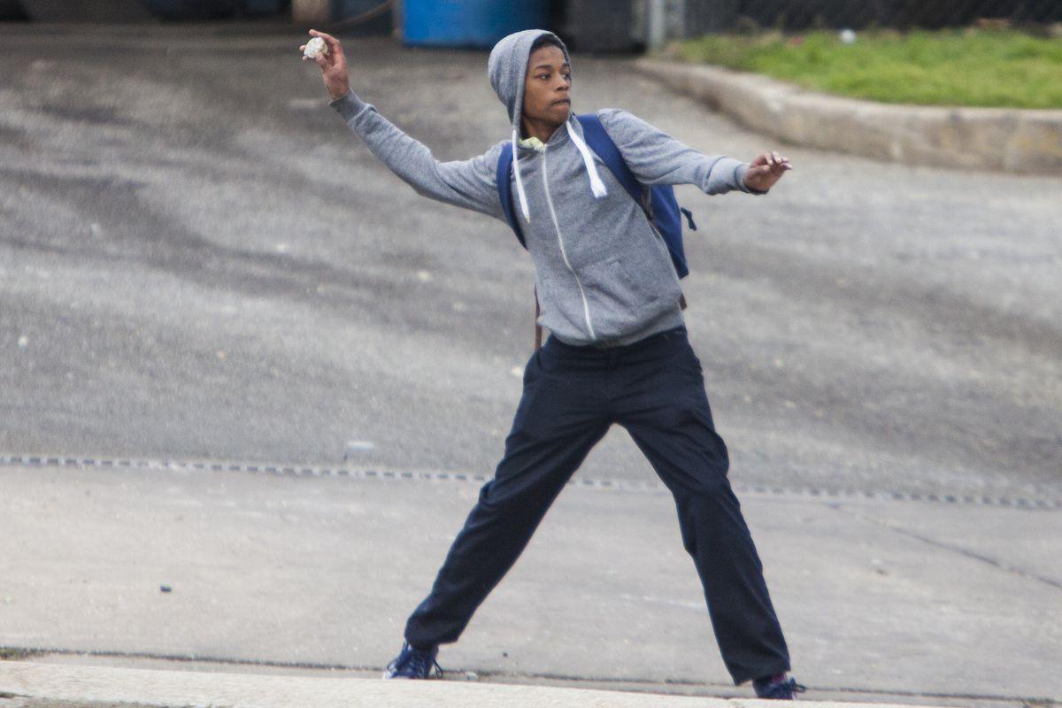 Baltimore protester throws rock