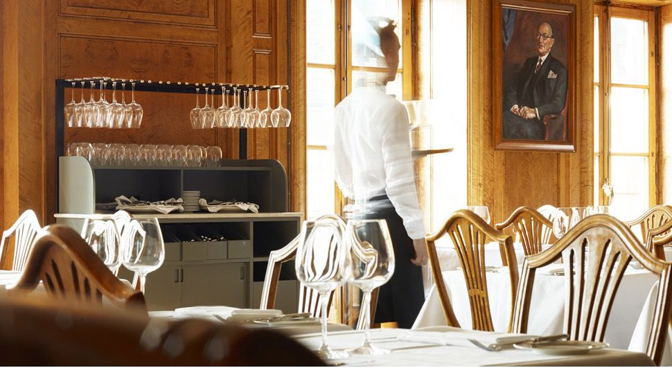 A server walks through a dining room with set formal tables and light-filled windows