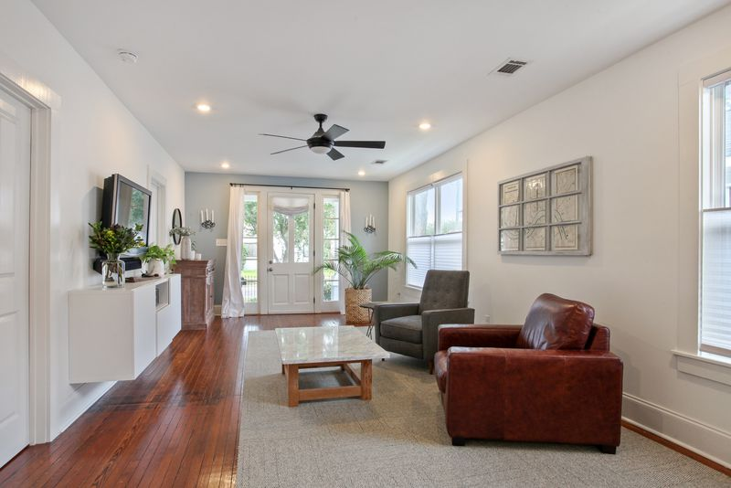 Living room with wood floors and big windows, plus ceiling fan and plants