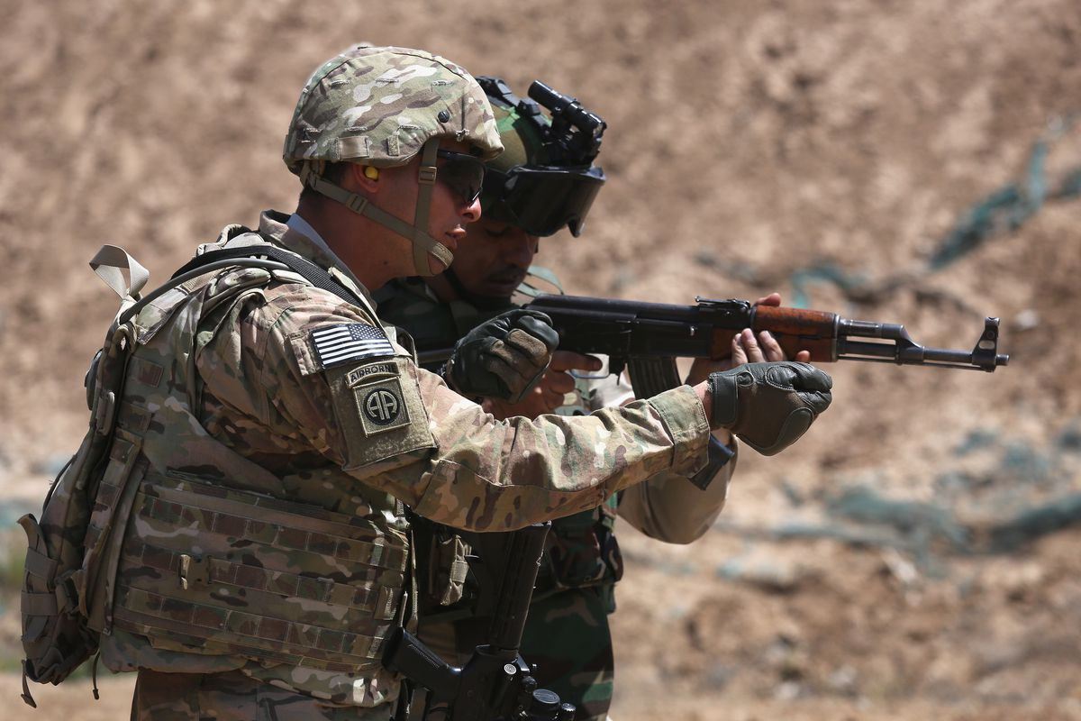 An American trainer works with an Iraqi army soldier in April.