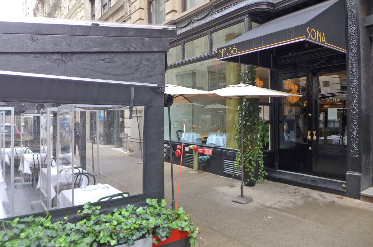 A restaurant with a black facade on the right, on the left is black wooden outdoor dining structure with white tables visible through the windows.