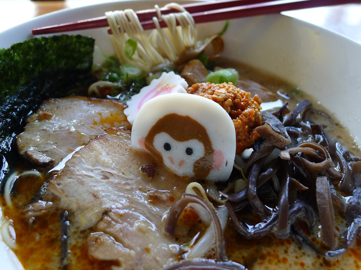 A bowl of noodles with a fish cake sticking out that features a picture of a monkey's face...