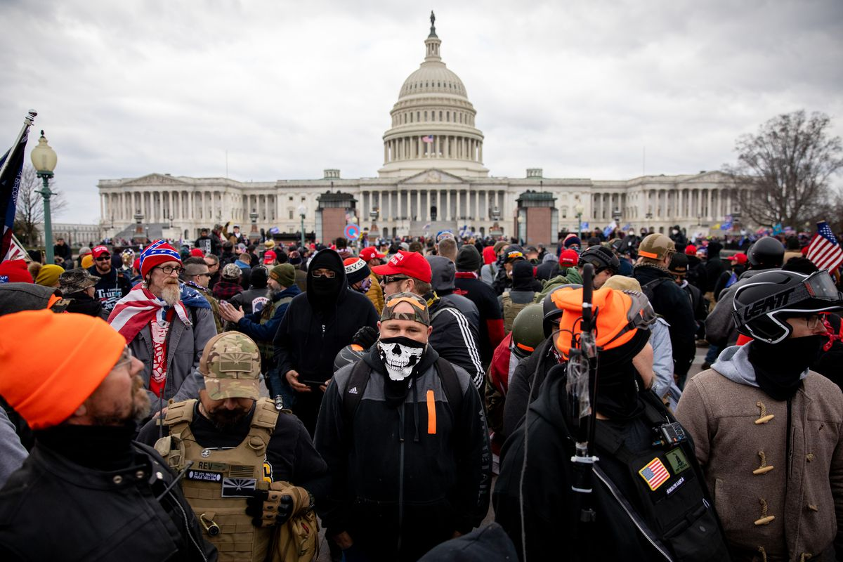 A mass of people, some in Confederate flag hats, others in helmets, bulletproof vests, and camouflage, stand shoulder to shoulder, with the white dome of the Capitol building behind them.