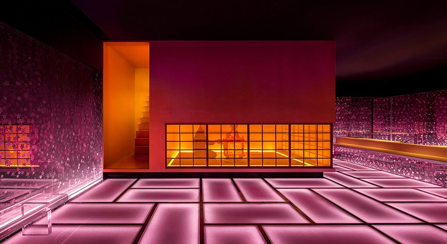 The interior of a sushi restaurant with glowing pink walls and floors.