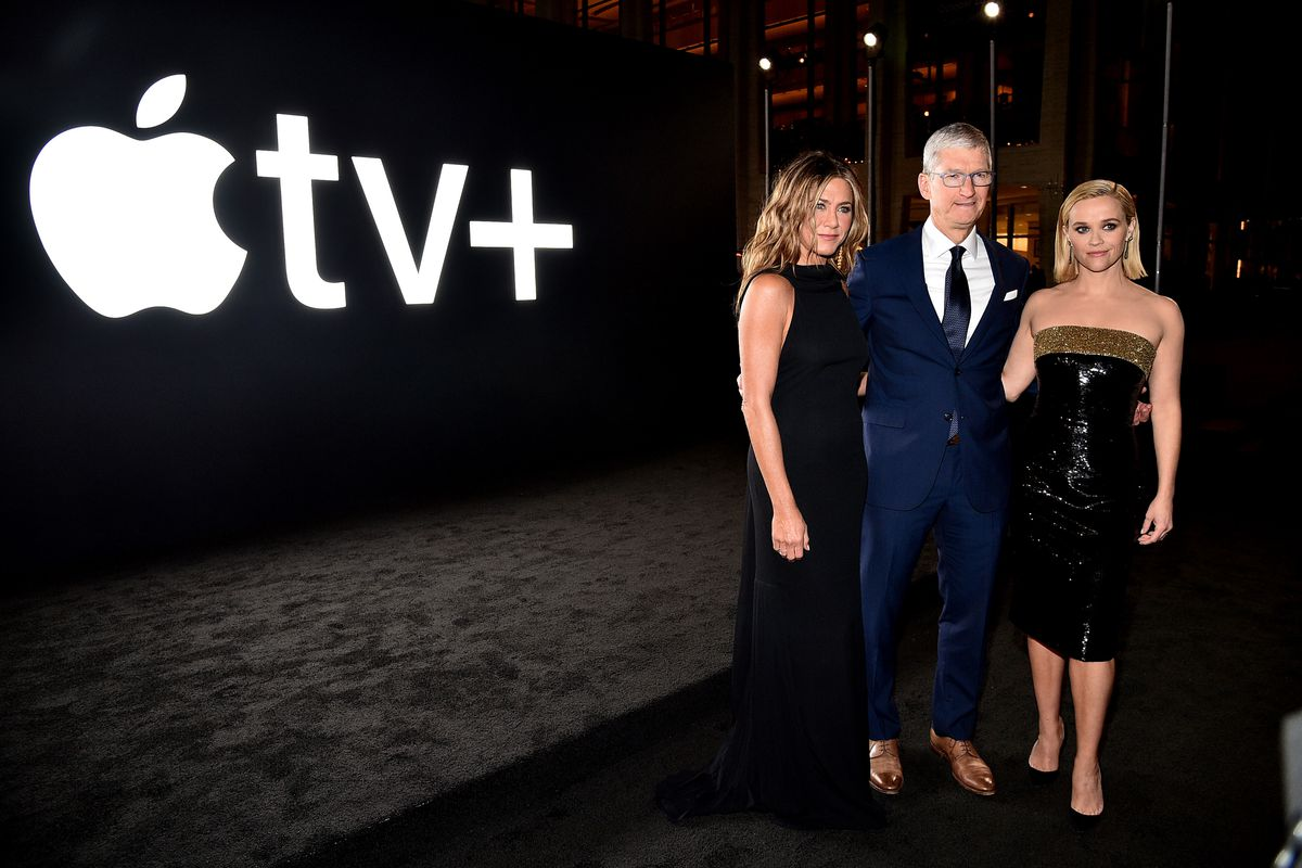 """Apple CEO Tim Cook stands flanked by Jennifer Aniston and Reese Witherspoon in front of a sign with the Apple logo and the then """"tv+."""""""