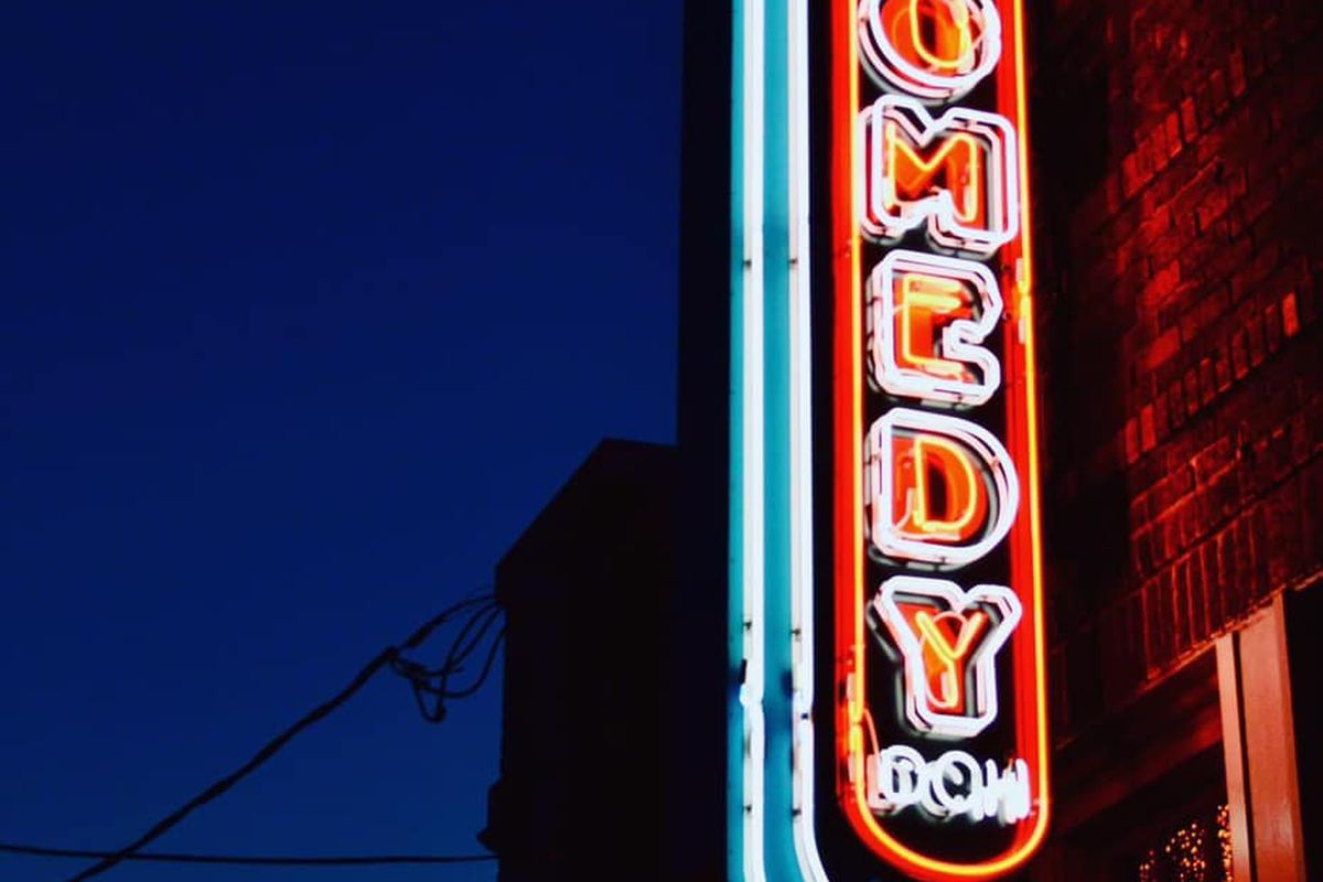 """a neon sign with an arrow pointing to a brick building. the sign reads """"comedy"""" in white and red neon letters"""