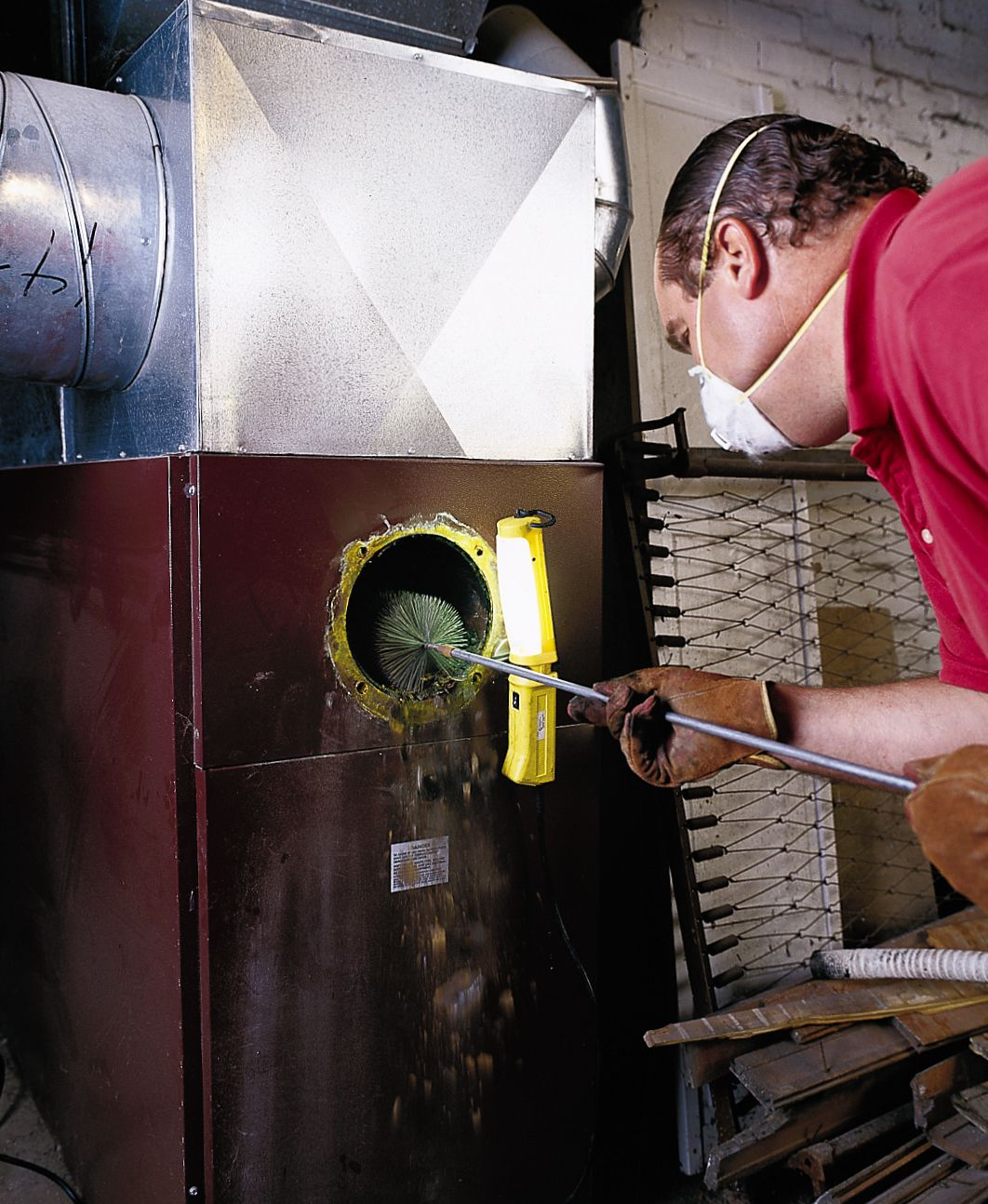 Person cleaning the combustion chamber during an annual furnace servicing.