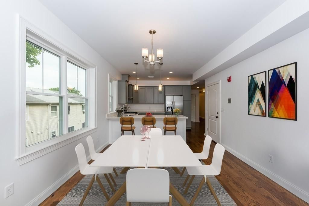 A long dining room with a table and chairs taking up much of it, and the room leads to a kitchen.