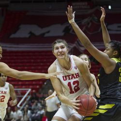Utah Utes forward Emily Potter (12) goes to the basket while guarded by Oregon Ducks forward Satou Sabally (0) and Oregon Ducks forward Oti Gildon (32) during the Utes' 84-68 loss at the Jon M. Huntsman Center in Salt Lake City on Sunday, Jan. 28, 2018.