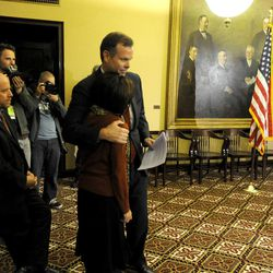 Utah Attorney General John Swallow embraces his wife Suzanne after a press conference announcing his resignation at the Capitol in Salt Lake City on Thursday, Nov. 21, 2013. Swallow cut a deal with the lieutenant governor's office to resign in order to avoid facing criminal charges. A report from the special counsel the office hired to investigate alleged election law violations recommended that Swallow be charged with three misdemeanors, a source said. In lieu of the criminal charges, the office negotiated a deal calling for only civil sanctions if Swallow would step down. The deal would prevent his election from being invalidated in a court action and his office from being up for grabs in a special election.
