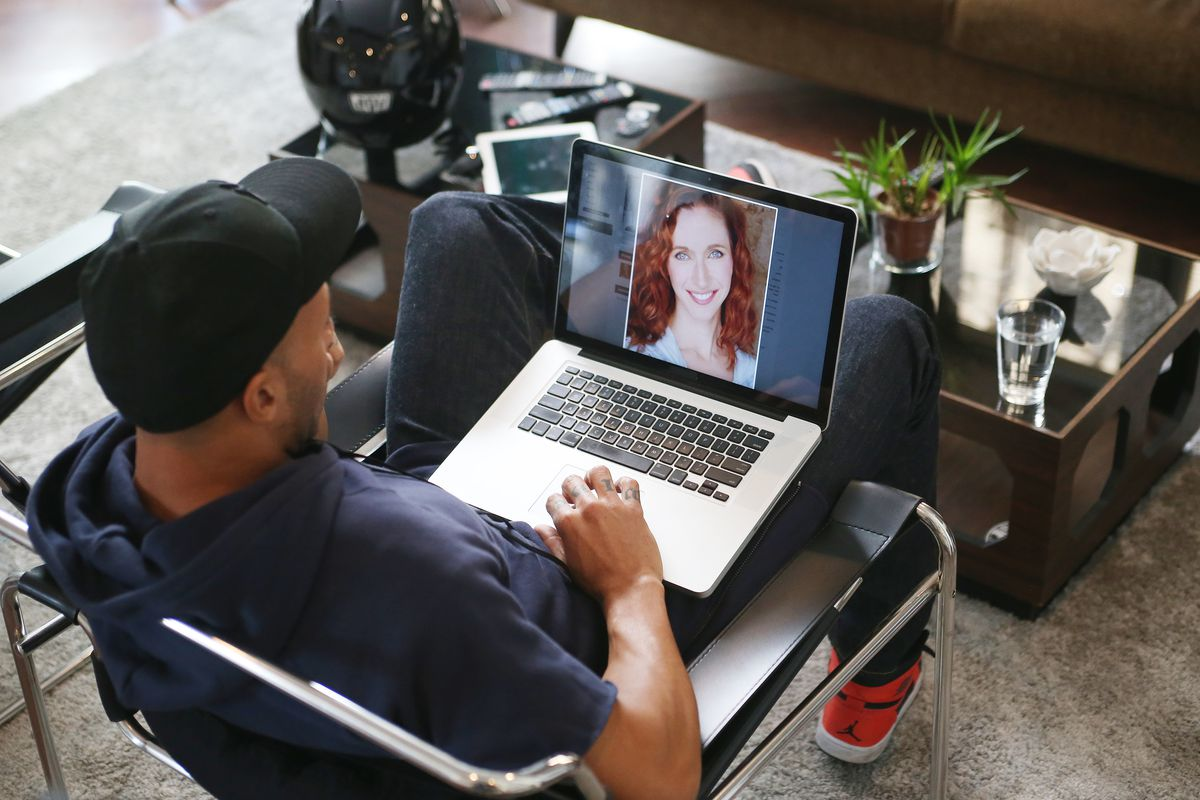 A person sits and looks at a picture on a dating website on a laptop screen.