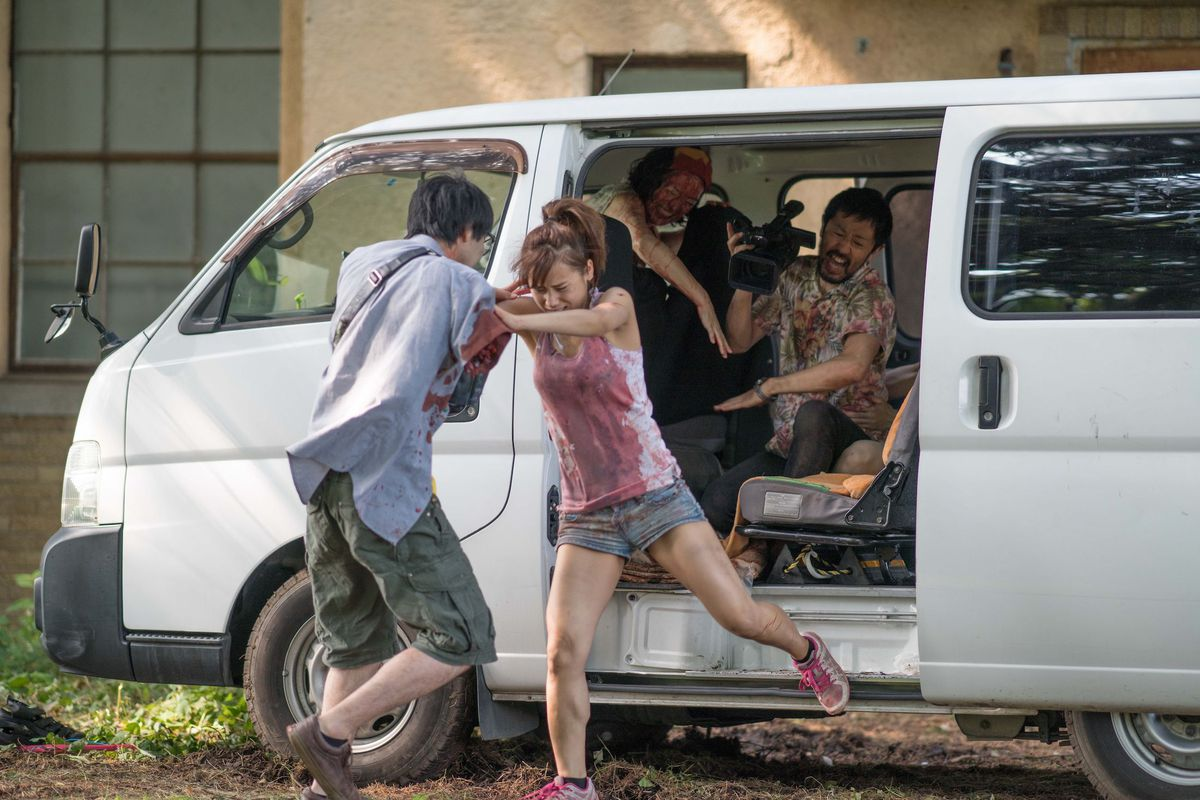 the cast of one cut of the dead fight for their lives from a zombie attack in a white van