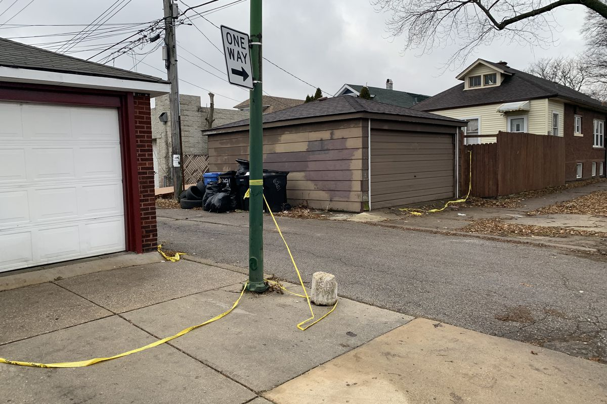 Yellow police tape remained at the north exit of an alley in the 6200 block of South Mozart where two men were killed during a shootout Monday morning.