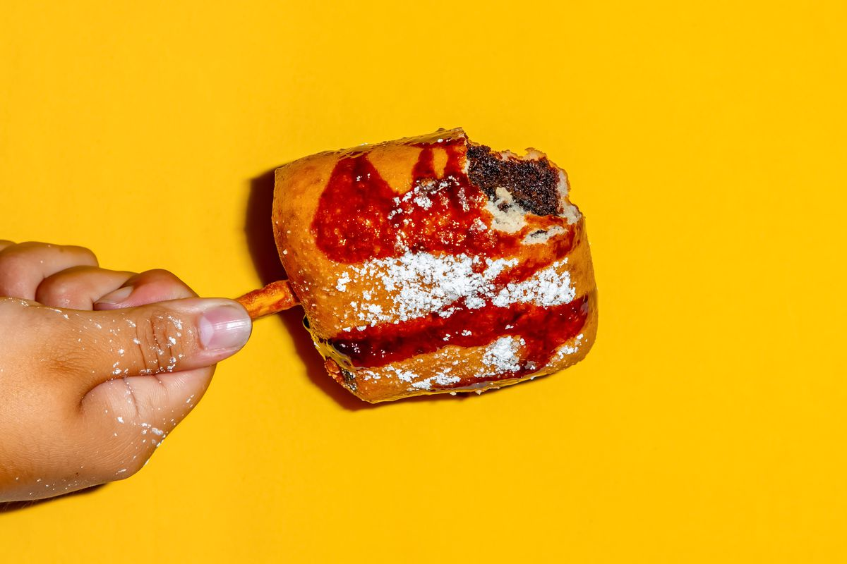 A hand holding a deep-fried brownie on a stick against a yellow background