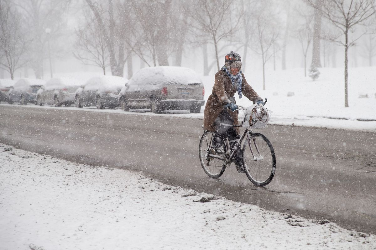 A woman on a bike rides through a snow street in Chicago.