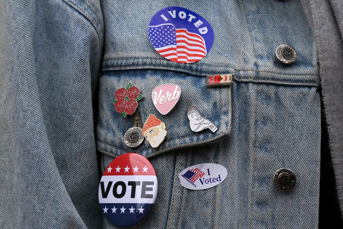 A person poses voting stickers and pins.