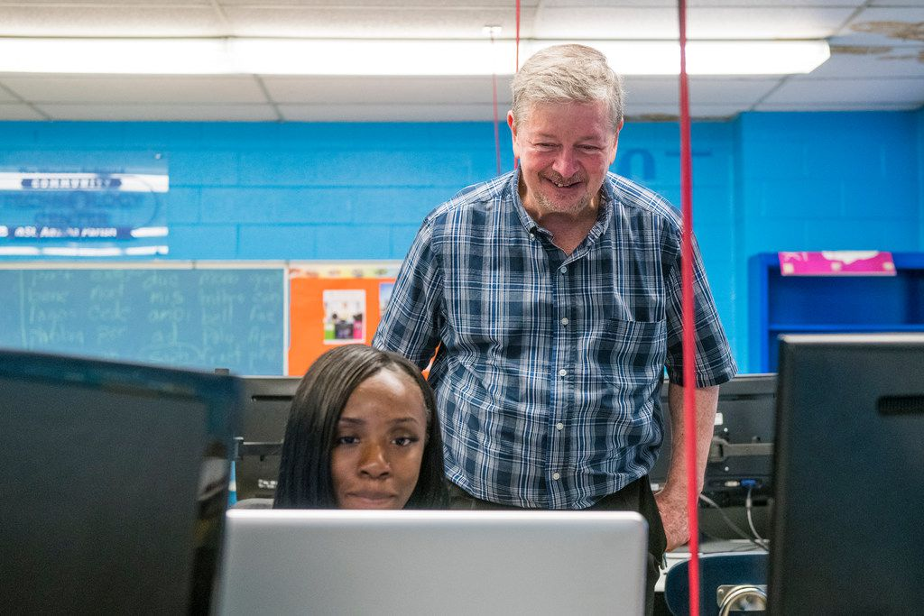 St. Agatha pastor, the Rev. Larry Dowling looks over Alexis Norman's shoulder, as the 21-year-old works during a session of the News School, a program the church provides to high-school students and young adults in the community.   Tyler LaRiviere/Sun-Tim