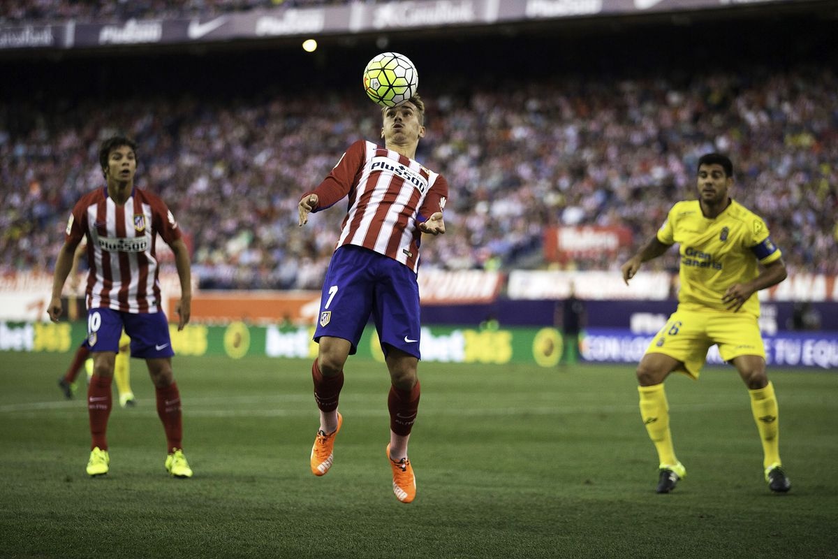 Antoine Griezzman fields a header against Las Palmas while Oli Torres watches on