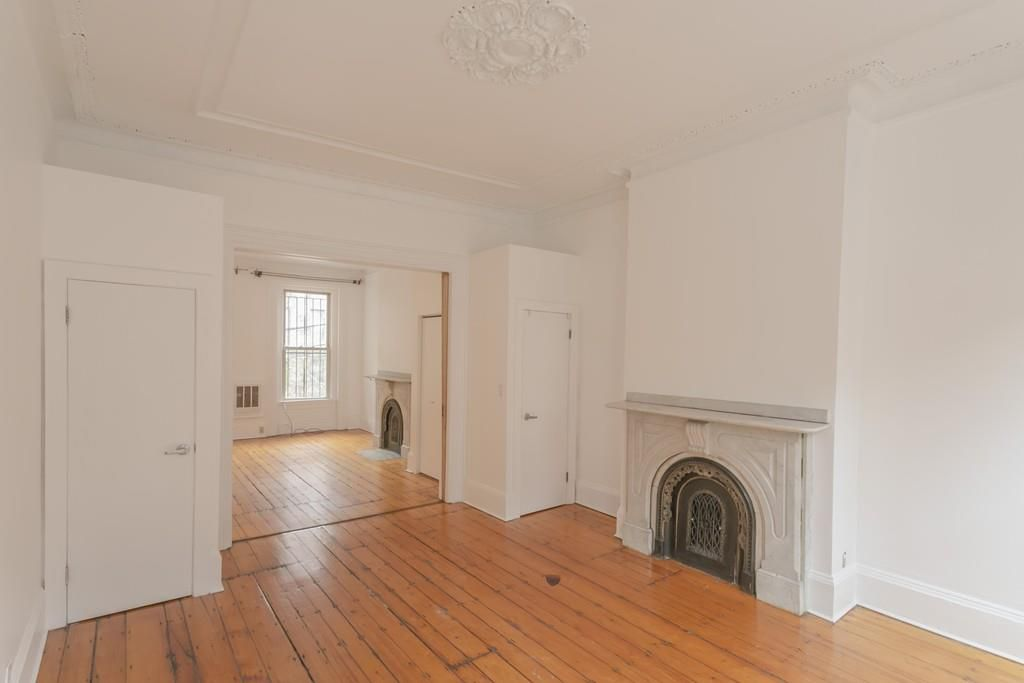 Empty rooms next to each other with a fireplace in each.
