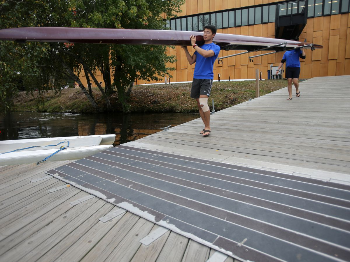 Two people carry a row boat on a ramp attached to a building.