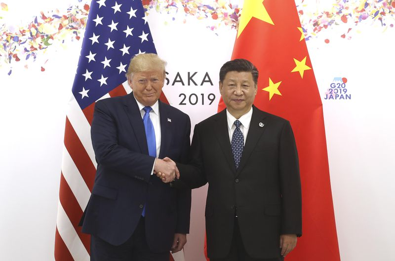 Trump and Xi shake hands in front of their respective flags at the G20.