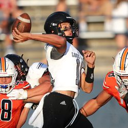 Lone Peak quarterback Jonah Heimuli gets the pass off just ahead of the rush as Lone Peak and Timpview play in a high school football game in Provo on Friday, Aug. 14, 2020.