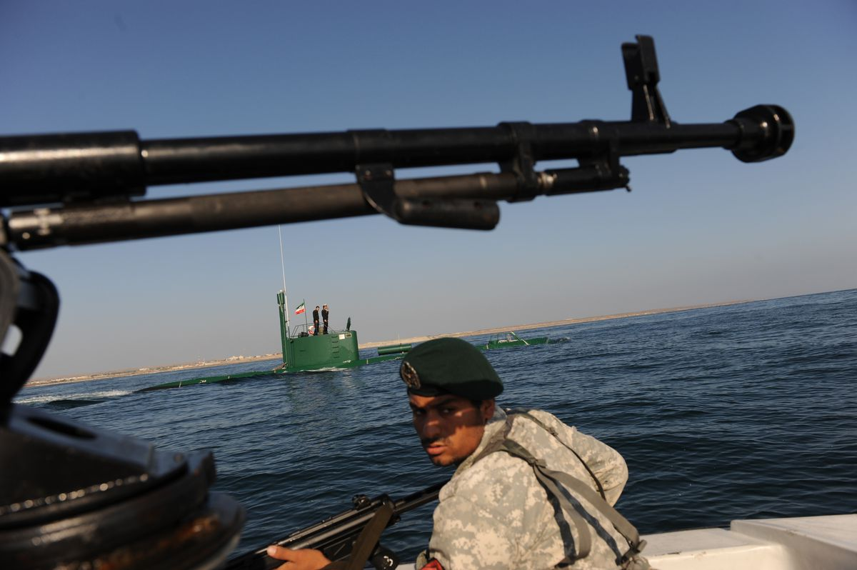 "An Iranian Army soldier stands guard on a military speed boat, passing by a submarine during the ""Velayat-90"" navy exercises in the Strait of Hormuz on December 28, 2011."
