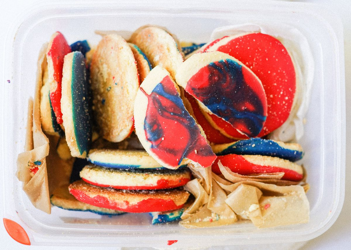 Red and blue iced sugar cookies, with one broken on the top, in a clear Tupperware container.