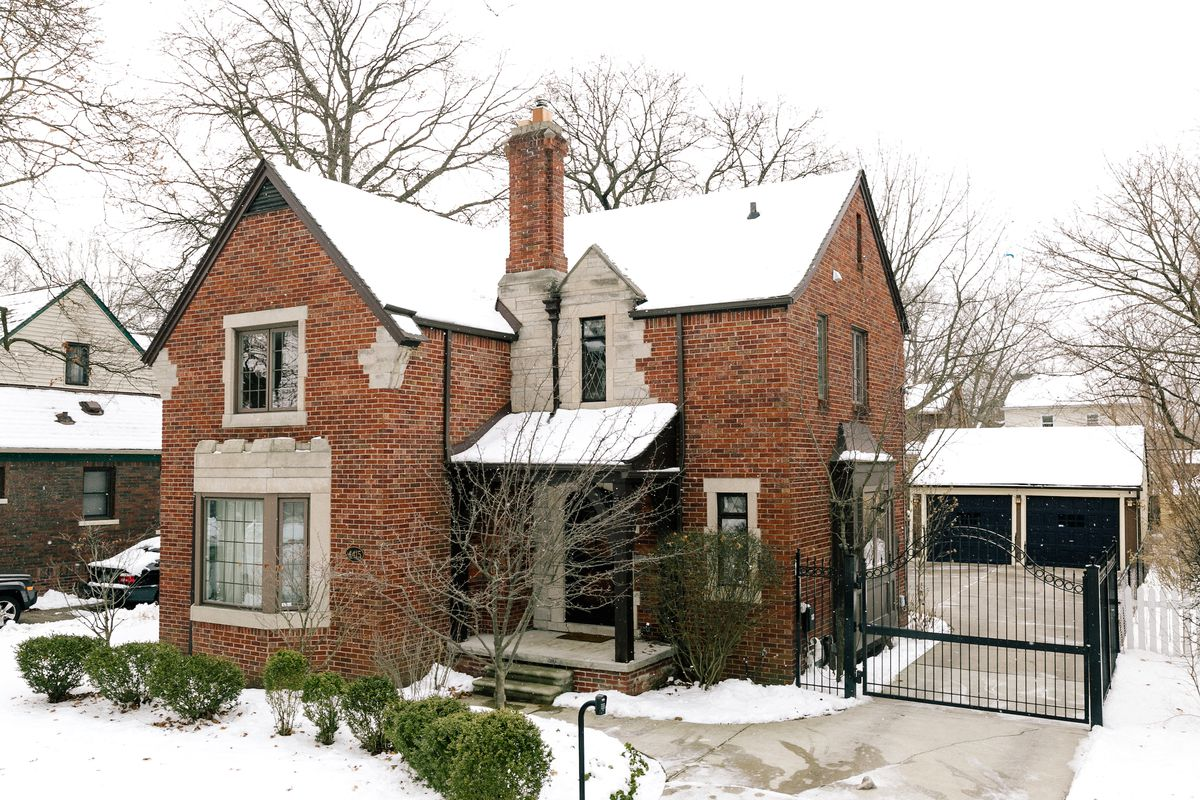 Brick Tudor Revival with stone accents around windows and a gated driveway. There's snow on the ground and the roof of the house.