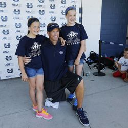 Utah State University football coach Matt Wells poses for a photo with his daughters Ella and Jadyn during a kids football camp in Logan Friday, June 12, 2015.