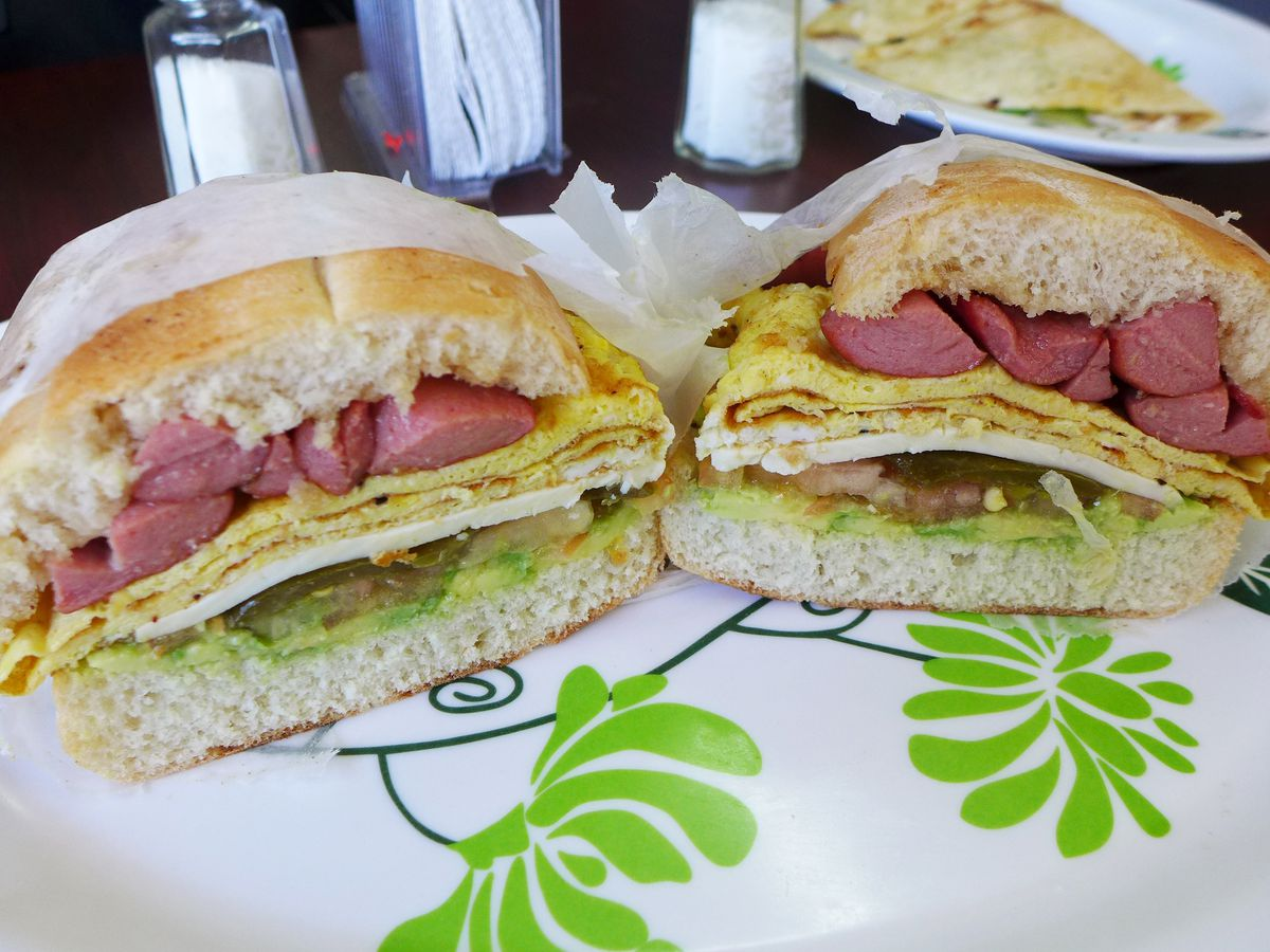 An overstuffed round sandwich with hot dogs, white cheese, and avocado, among other ingredients.